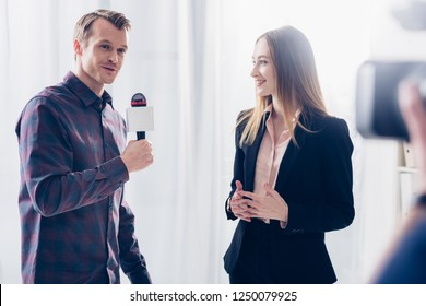 beautiful businesswoman in suit giving interview to journalist in office