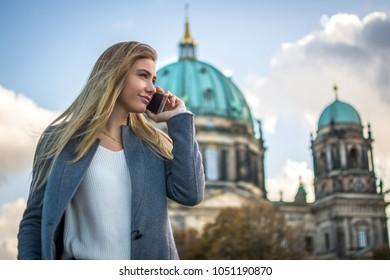 Beautiful businesswoman talking on mobile phone while walking through Berlin city street.