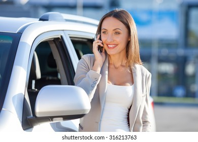 Beautiful businesswoman is talking on the mobile phone and smiling. She is standing near her car and looking forward with joy