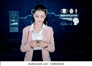 Beautiful businesswoman using Face ID identification for scanning and identify her face on mobile phone