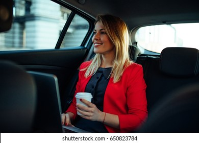 Beautiful businesswoman using laptop while sitting on a backseat of a car.