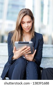 Beautiful businesswoman using a tablet outdoor in the city