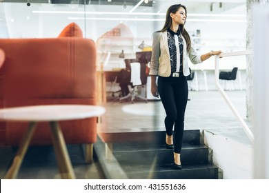 Beautiful businesswoman walking down the stairs while holding the railing