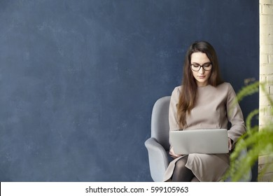 Beautiful businesswoman working on laptop while sitting in modern loft office. Dark blue wall background, day light
