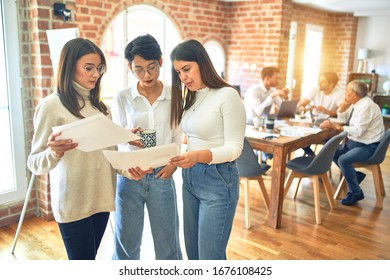 Beautiful businesswomen smiling happy. Standing with smile on face working together reading documents using smartphone at the office