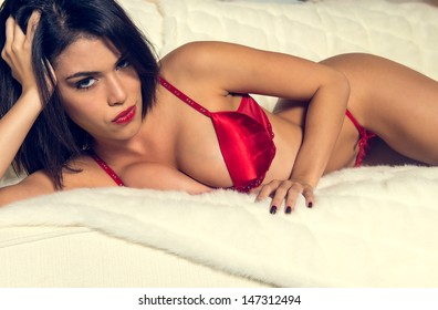 Beautiful busty brunette woman in sexy red lingerie lying on a bed looking at the camera with a sultry seductive look