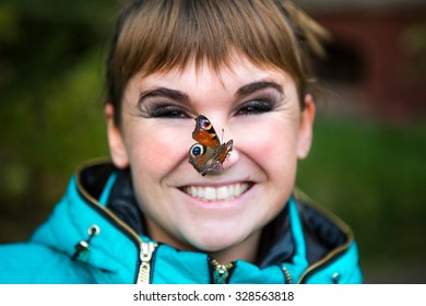 Beautiful butterfly sitting on the girl nose
