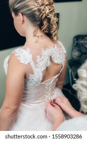 Beautiful buttons on the white dress of the bride. Hands girlfriend buttoned buttons on the bride's dress.