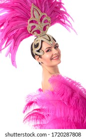 Beautiful cabaret dancer in a headdress of feathers and rhinestones. An attractive girl with a fan of pink feathers. Isolated on a white background.