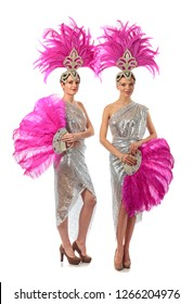Beautiful cabaret dancers in costumes with rhinestones and purple feathers isolated on white background. Attractive girls with perfect makeup and headdress from natural feathers.