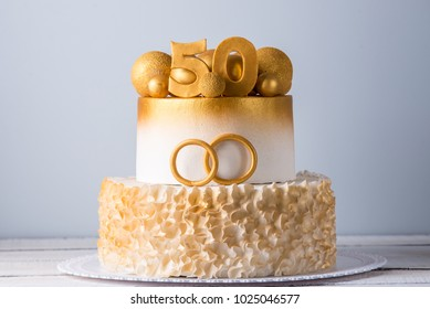 A beautiful cake for the 50th anniversary of the wedding decorated with gold balls and rings. The concept of festive desserts