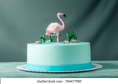 A beautiful cake, decorated with a figure of pink flamingos in the pond. The concept of the Original design of desserts