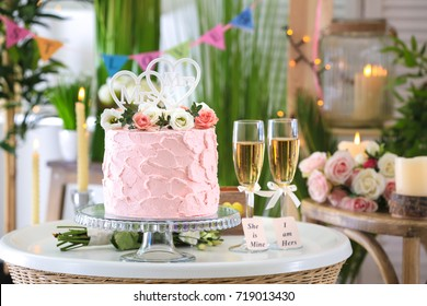 Beautiful cake for lesbian wedding decorated with flowers on table in the room