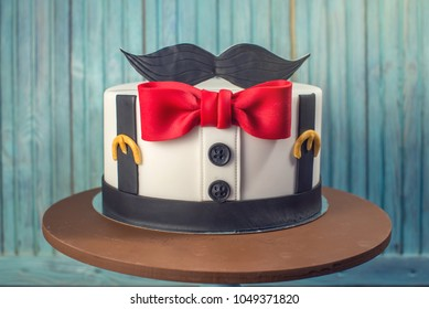 Beautiful cake for men, decorated in the form of a suit with a bow tie. The concept of the desserts for the birthday boy