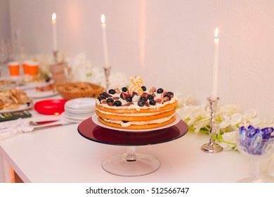 Beautiful Cake With Open Layers Stands On A White Table Behind There Are Candles