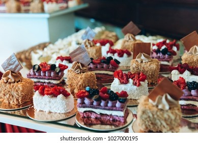 Beautiful cakes on wedding candybar table with berries, caramel and coconut