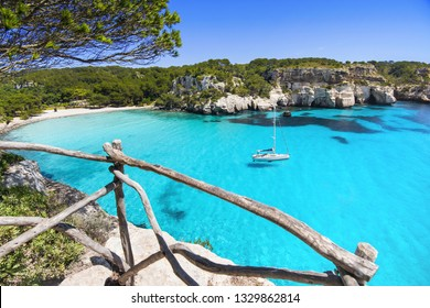 Beautiful Cala Macarella beach, Menorca island, Spain. Sailing boat in a bay. Summer fun, enjoying life, yachting, travel and active lifestyle concept