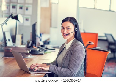 Beautiful call center agent browsing the internet on her computer