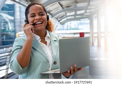 Beautiful Call center staff talking and provide services to customers via headphones and microphone cable at outside cityscape. Professionals with speech, service mind and information recording skills
