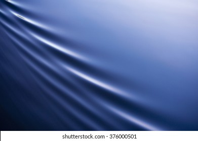 Beautiful, calm blue water is broken by elegant, diagonal ripples with lots of copy space.