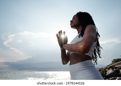 Beautiful calm fit young woman keeping hands in namaste mudra when meditating on sea beach