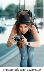 The beautiful calm girl student in a stylish casual hat photographs something with small digital camera. Urban outdoor travel scene