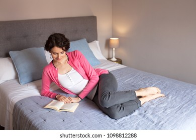 Beautiful calm middle age woman laying relaxing on home bed reading book. Mature female intellectual enjoying reading story, leisure recreation lifestyle, hobbies interests smiling indoors.