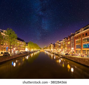 Beautiful calm night view of Amsterdam city. Night time illuminations of Dutch style buildings with reflections on water canal. Netherlands, Europe.