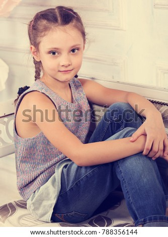 e175a3b6c Beautiful calm smiling kid girl sitting on the bench in blue jeans and fashion  blouse looking