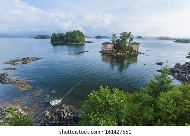 Beautiful calm summer, seascape with boat and houses on tiny forested islands in Sitka Sound on Baranof Island, Alaska