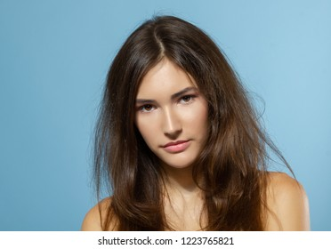 Beautiful calm teen girl looking at camera over blue background. Young pretty woman posinng at studio.