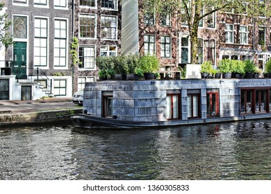 Beautiful and calm view of the houseboat in the capital of the Netherlands - Amsterdam. Ordinary scene of the water, houses and a houseboat. Romantic city. Typical scene of the Dutch city.