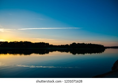 A beautiful and calming sunset accented by a long narrow cloud, a few days after midsummer, reflected on the water of a cove on the Island of Nicklösa in the Åland Islands, Finland.