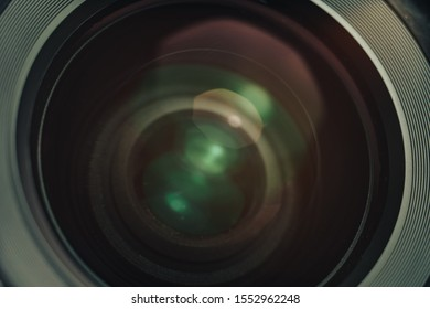 Beautiful camera lens with yellow and pink light of glass on a black background.