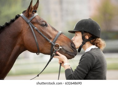 Beautiful Candid Portrait of a Happy Teenager Kissing a snout of her Horse Outdoors