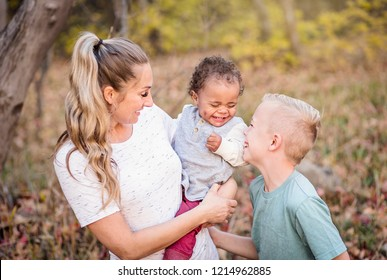 Beautiful candid portrait of a mother playing with her cute children. Mother and her two boys spending time together in the outdoors and laughing together. Great adoption or blended family photo