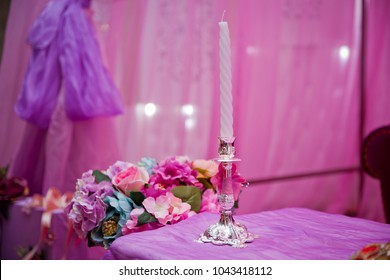 Beautiful candle on pink background . Candle in candlestick burning . Retro Candelabra With Burning Candles . Burning Candle In Old Silver Candlestick