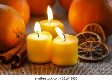 Beautiful candles and juicy oranges on jute table cloth