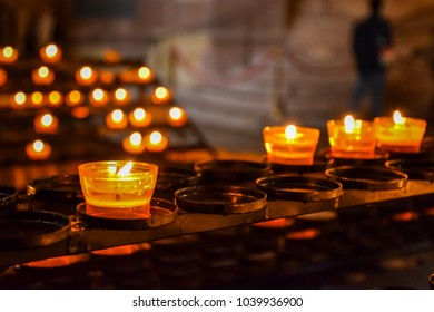 Beautiful candles placed in the small glass in the church with blurred background
