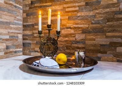 Beautiful candlestick with burning candles, a silver glass for blessing and a white yarmulke. Background stone wall. Still life with objects Judaica. Concept of artistic photography