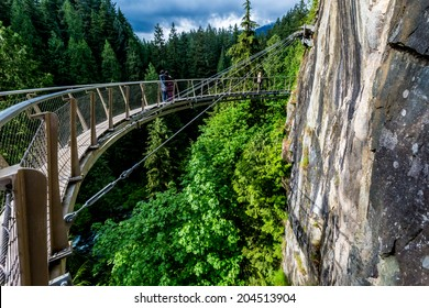 Beautiful Capilano Cliff Walk Suspension Bridge with Tourists Enjoying the View, in Vancouver.