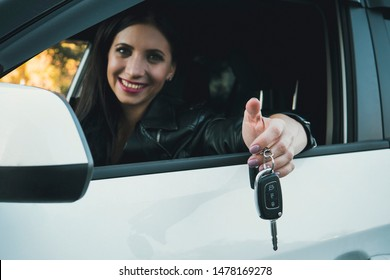 Beautiful car driver woman smiling showing new car keys and car. Caucasian girl sitting in automobile, smiling and demonstrating keys. Female owner of vehicle. Woman is happy to purchase auto