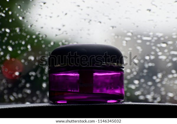 Beautiful car fragrance bottle of a car with blurry raindrops background unique photo