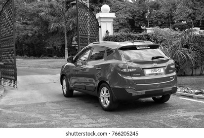 Beautiful car leaves outside towards the big wrought iron gates of a residential area in Ghana, West Africa. Black and White Photography. Accra, Ghana - August 18, 2013