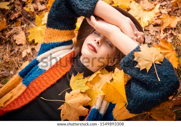 Beautiful carefree girl lies on yellow fallen leaves at the autumn park. Sunny day. Autumn beauty, fashion.
