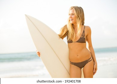 Beautiful carefree happy surfer girl on the beach at sunset. Beach culture lifestyle concept.