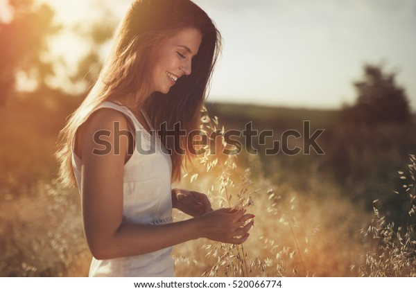 Beautiful carefree woman in fields being happy outdoors