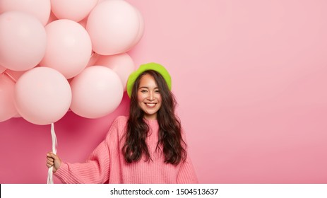 Beautiful carefree woman holds air balloons, wears green beret and rosy sweater, celebrates mums birthday, stands indoor against pink background, free space for your promotional information.