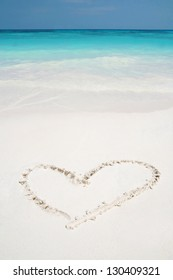 Beautiful Caribbean tropical beach with a heart drawn on white sand and green ocean, love hearts sign on beach background