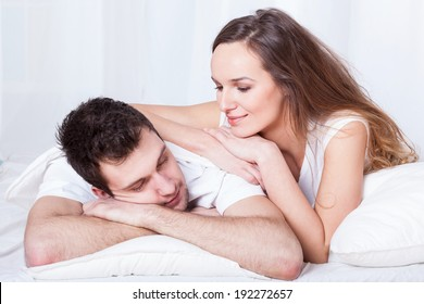 A beautiful caring woman lying on top of her sleeping husband